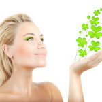 woman holding four leaf clovers